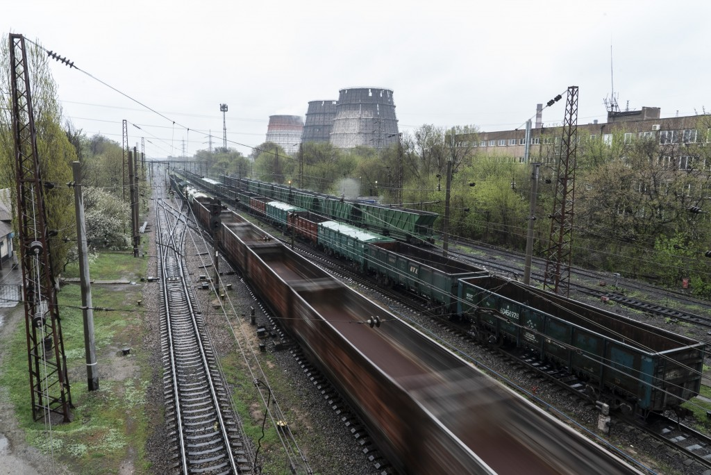 In this photo taken on Monday, April 15, 2019, trains move past industrial facilities in Kryvyi Rih, in eastern Ukraine. The country votes Sunday, Apr...