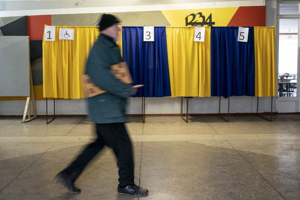 In this photo taken on Monday, April 15, 2019, a man with a chess set walks past voting booths set up in a school in Kryvyi Rih, in eastern Ukraine. T