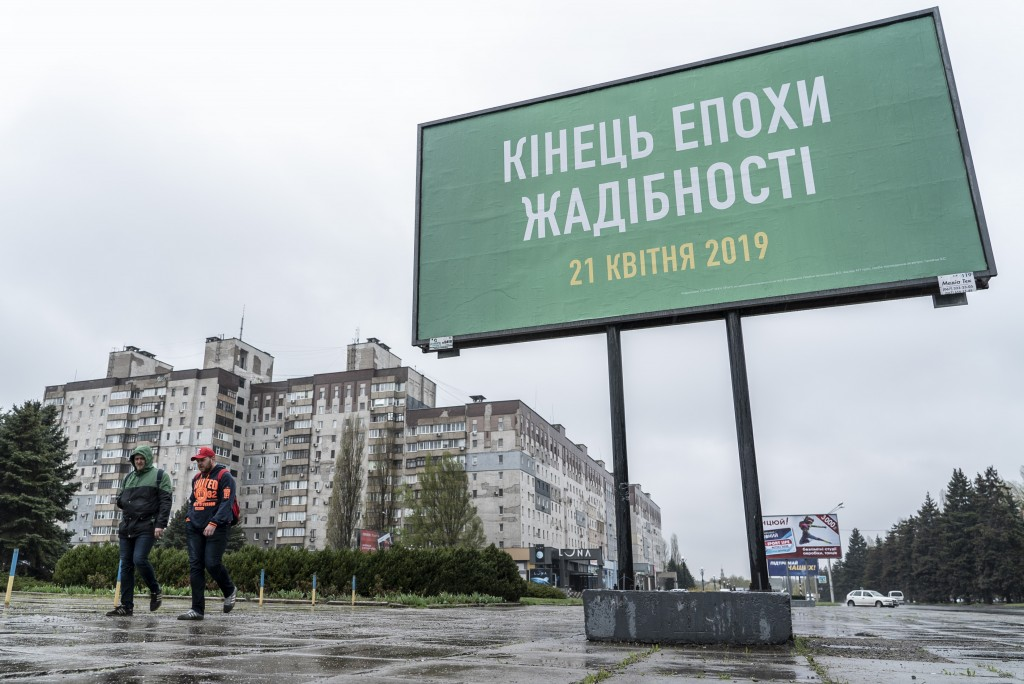 In this photo taken on Monday, April 15, 2019, people in Kryvyi Rih, in eastern Ukraine, walk past a billboard supporting the campaign of presidential...