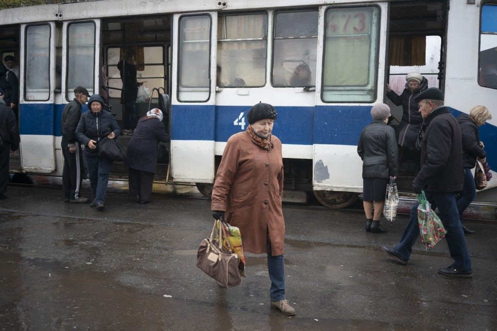 In this photo taken on Monday, April 15, 2019, a woman walks past a tram in Kryvyi Rih, in eastern Ukraine. The country votes Sunday, April 21, on whe