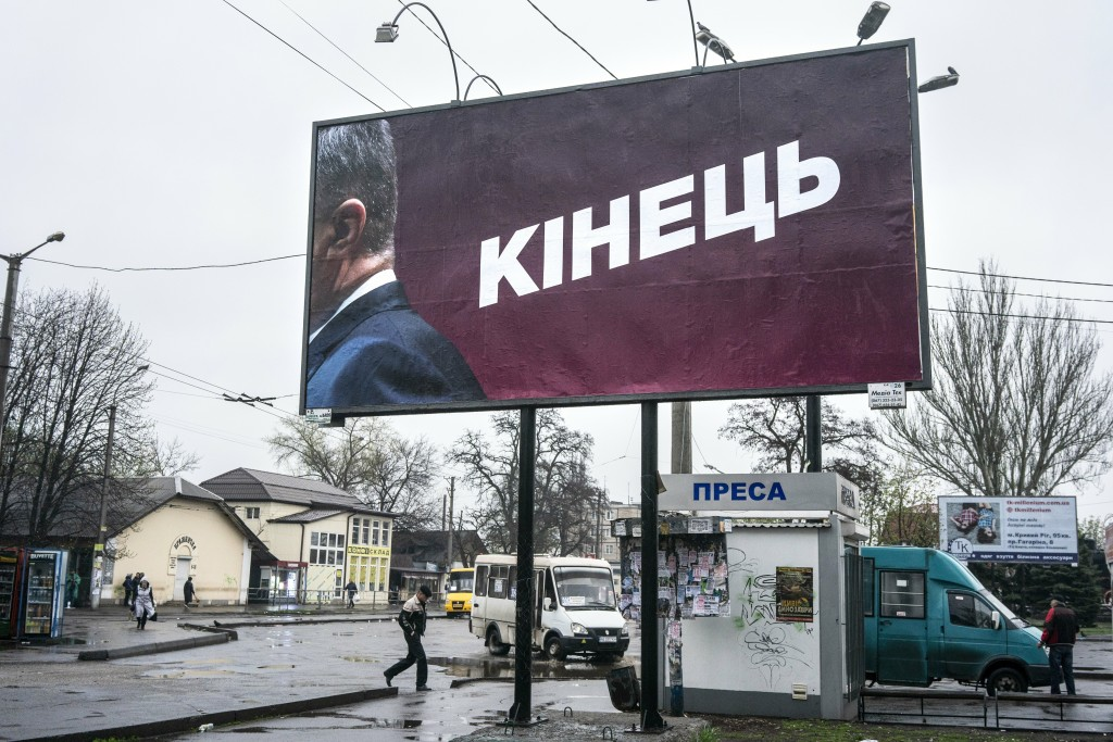 """In this photo taken on Monday, April 15, 2019, people in the city of Kryvyi Rih, Ukraine, walk past a billboard reading """"The End"""" ahead of Sunday, Apr"""
