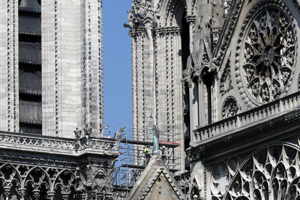 Workers prepare to remove a statue from the damaged Notre Dame cathedral, in Paris, Friday, April 19, 2019. Rebuilding Notre Dame, the 800-year-old Pa