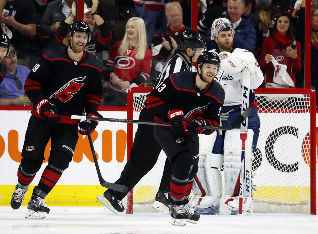Carolina Hurricanes' Warren Foegele (13) celebrates his goal with Dougie Hamilton (19) nearby during the first period of Game 4 of the team's NHL hock...