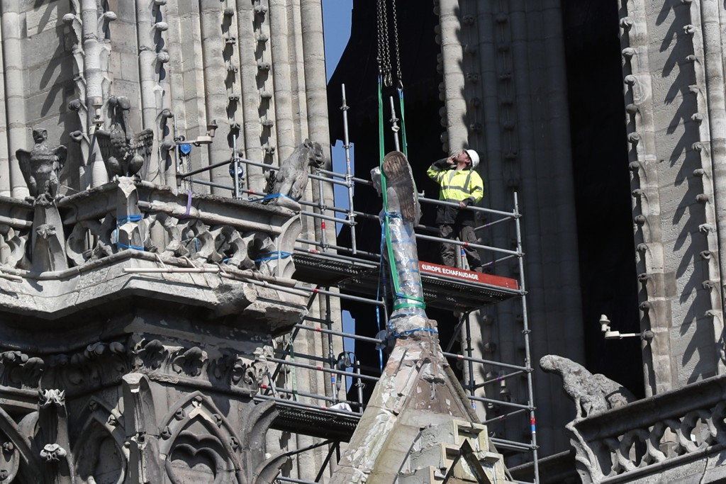A worker prepares to remove a statue from the damaged Notre Dame cathedral, in Paris, Friday, April 19, 2019. Rebuilding Notre Dame, the 800-year-old