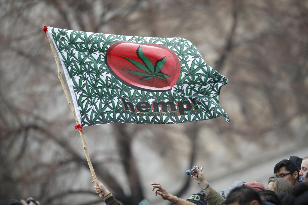 FILE - In this April 20, 2018 file photo an attendee hoists a flag during the Mile High 420 Festival in Denver. Potheads have for decades celebrated t