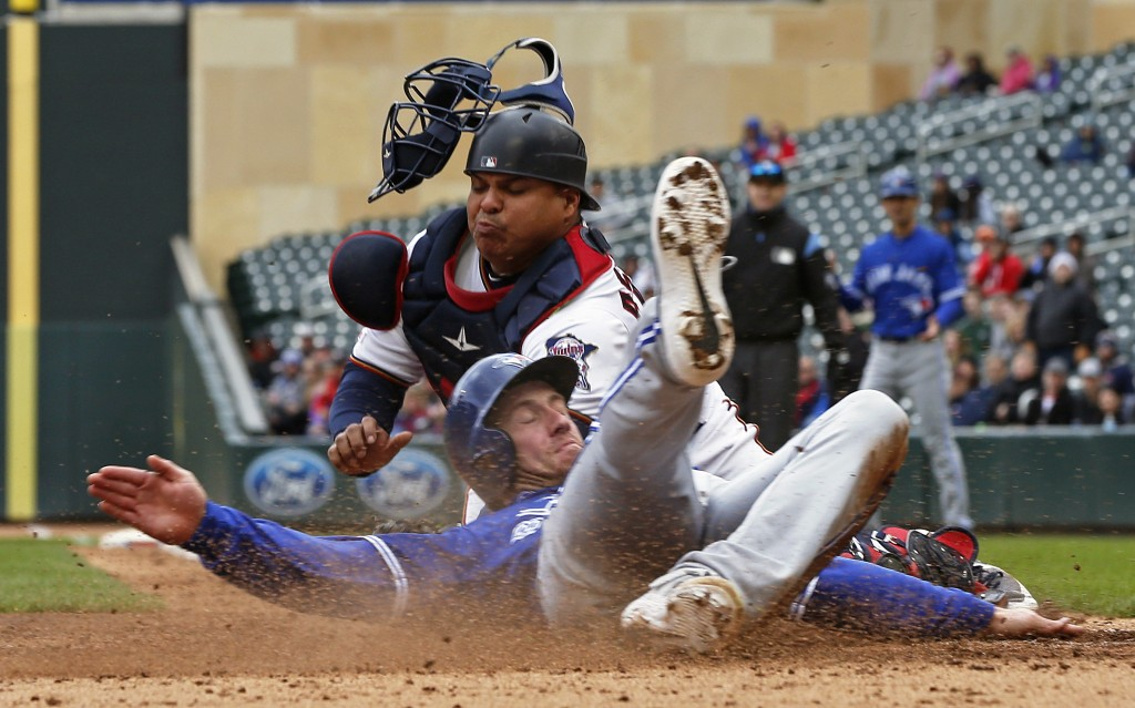 Toronto Blue Jays' Billy McKinney, right, beats the tag by Minnesota Twins catcher Willians Astudillo to score on a three-run, bases loaded double by ...