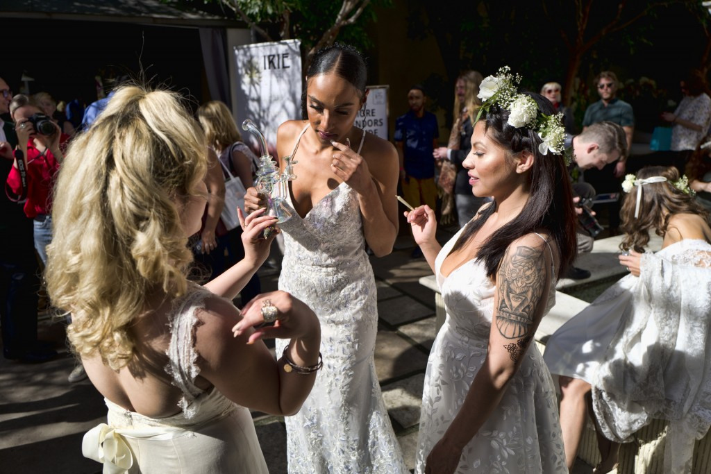 FILE - In this Jan. 26, 2019 file photo models wearing wedding dresses get ready smoke marijuana during the Cannabis Wedding Expo in Los Angeles. U.S.