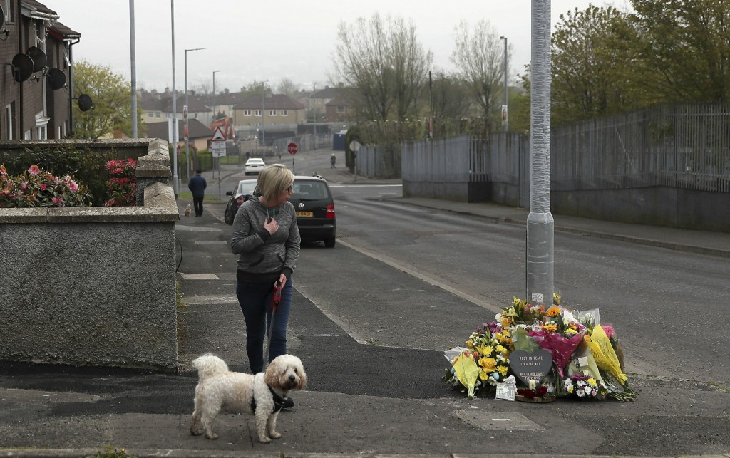 A woman reacts as she stops to pay her respects at the scene Saturday April 20, 2019, in Londonderry, Northern Ireland, where 29-year old journalist L...
