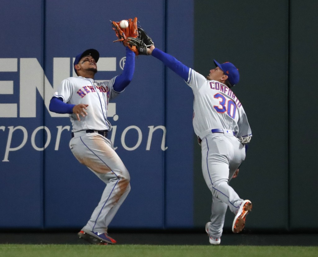 New York Mets center fielder Juan Lagares, left, nearly collides with right fielder Michael Conforto while catching a fly ball by St. Louis Cardinals'