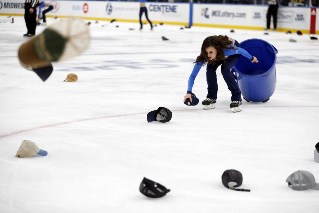 A member of the St. Louis Blues ice crew picks up caps after Blues' Jaden Schwartz scored a hat trick during the third period in Game 6 of an NHL firs...