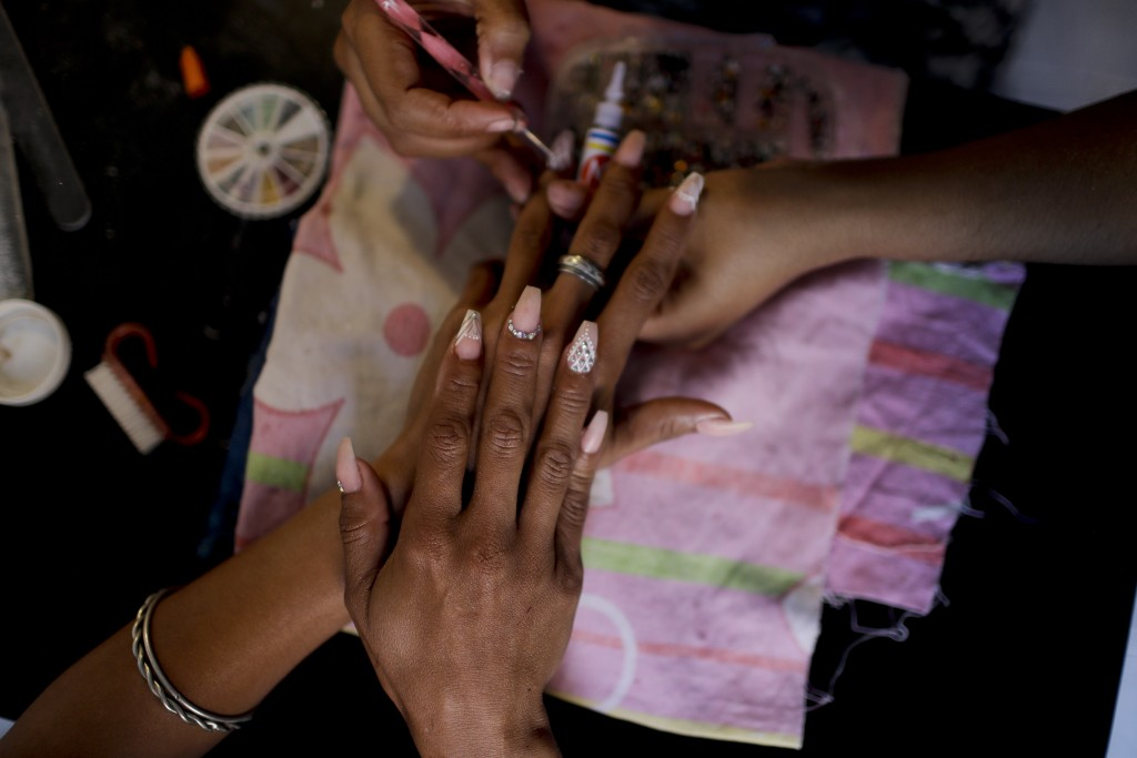 Yaris Colina gets her nails done at a beauty salon in Caracas, Venezuela, Friday, March 22, 2019. Local shops that sell beauty products are also reinv...