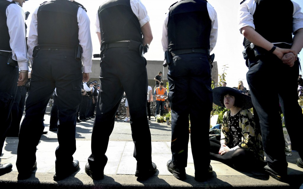 Police speak to a demonstrator on the main thoroughfare on Waterloo Bridge in central London, Saturday April 20, 2019.  Climate protesters with the en...