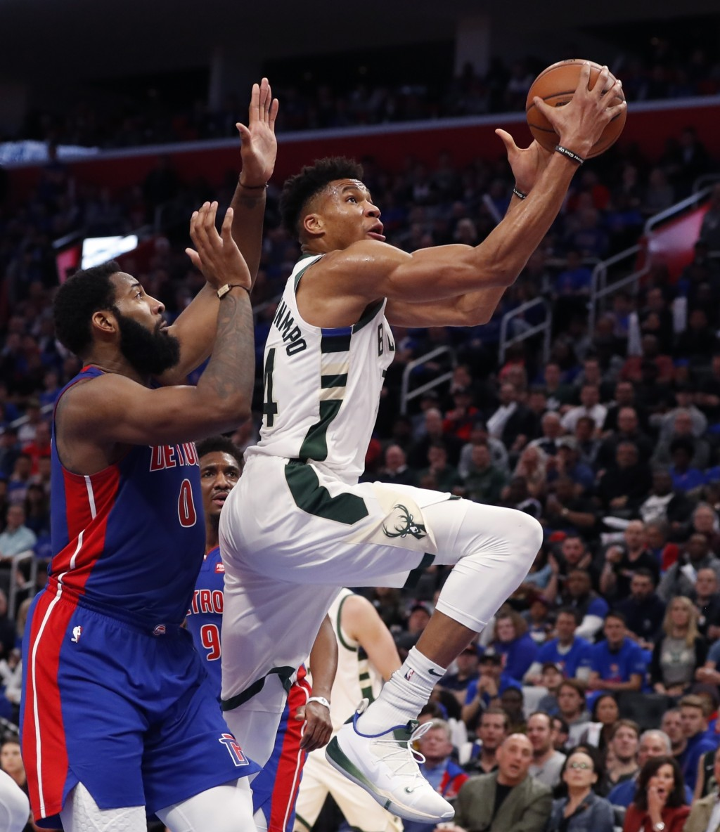 Milwaukee Bucks forward Giannis Antetokounmpo, right, makes a layup as Detroit Pistons center Andre Drummond defends during the first half of Game 3 o...