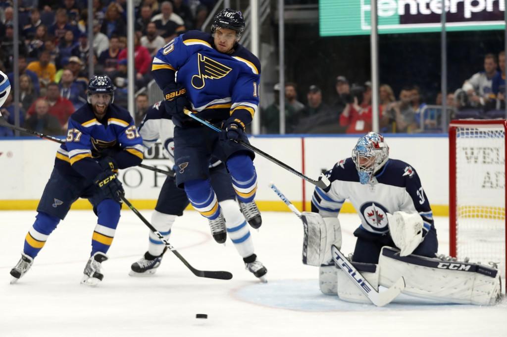 St. Louis Blues' Brayden Schenn (10) leaps to avoid a shot headed for Winnipeg Jets goaltender Connor Hellebuyck, right, as Blues' David Perron (57) w...