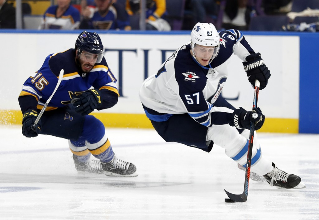 Winnipeg Jets' Tyler Myers (57) handles the puck as St. Louis Blues' Robby Fabbri (15)pursues during the second period in Game 6 of an NHL first-round...