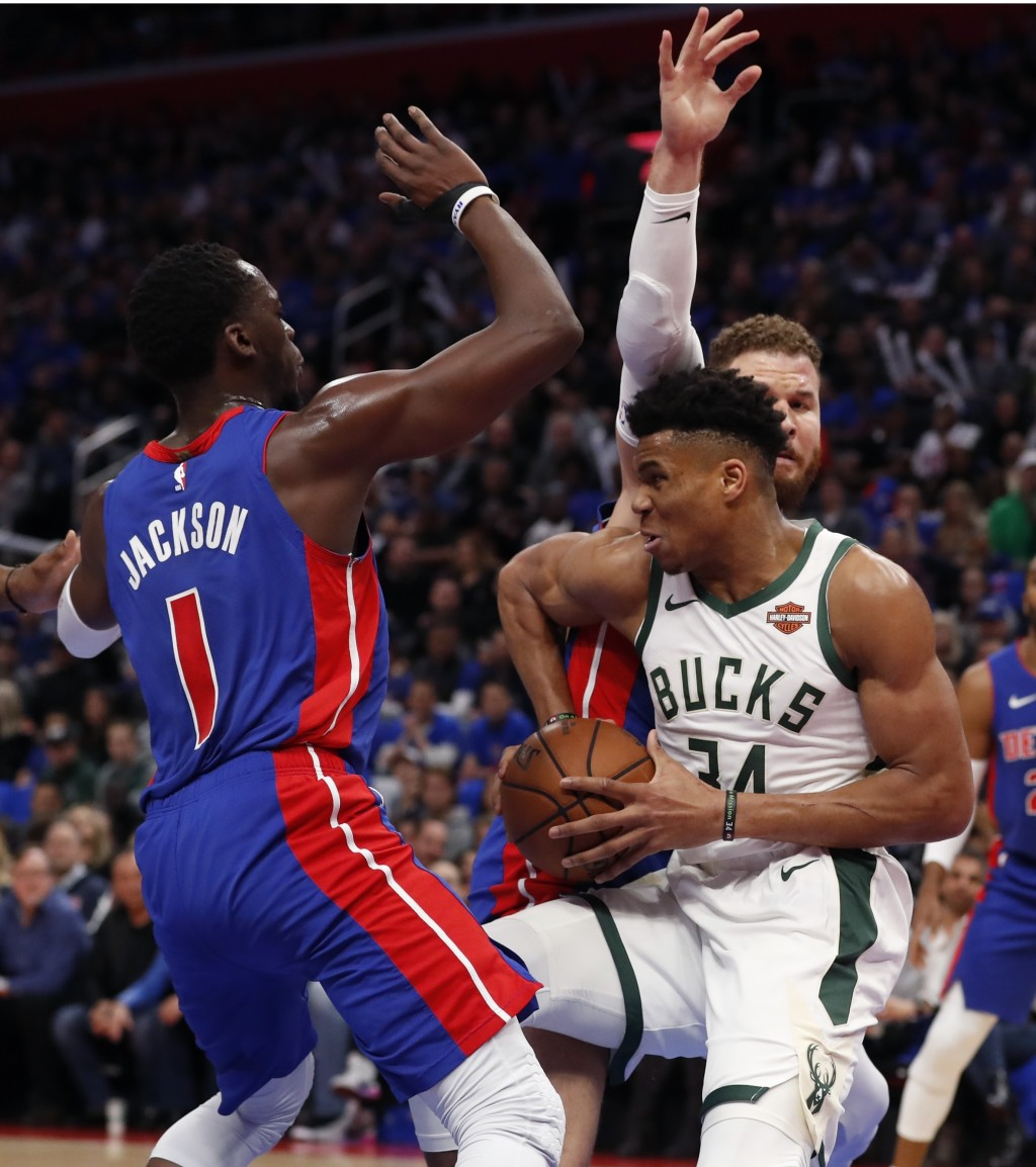 Milwaukee Bucks forward Giannis Antetokounmpo (34) controls the ball as Detroit Pistons guard Reggie Jackson (1) and forward Blake Griffin close in du...