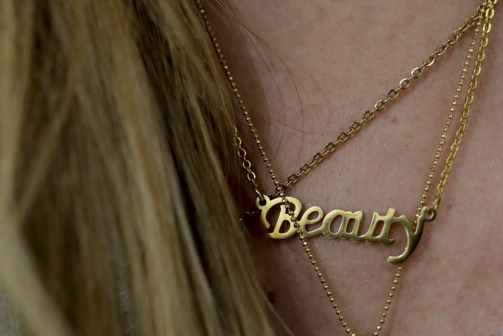 """Carolina Dejan wears a neckless featuring the word """"Beauty"""" at a beauty salon where she is getting extensions using real hair from women who sold thei"""