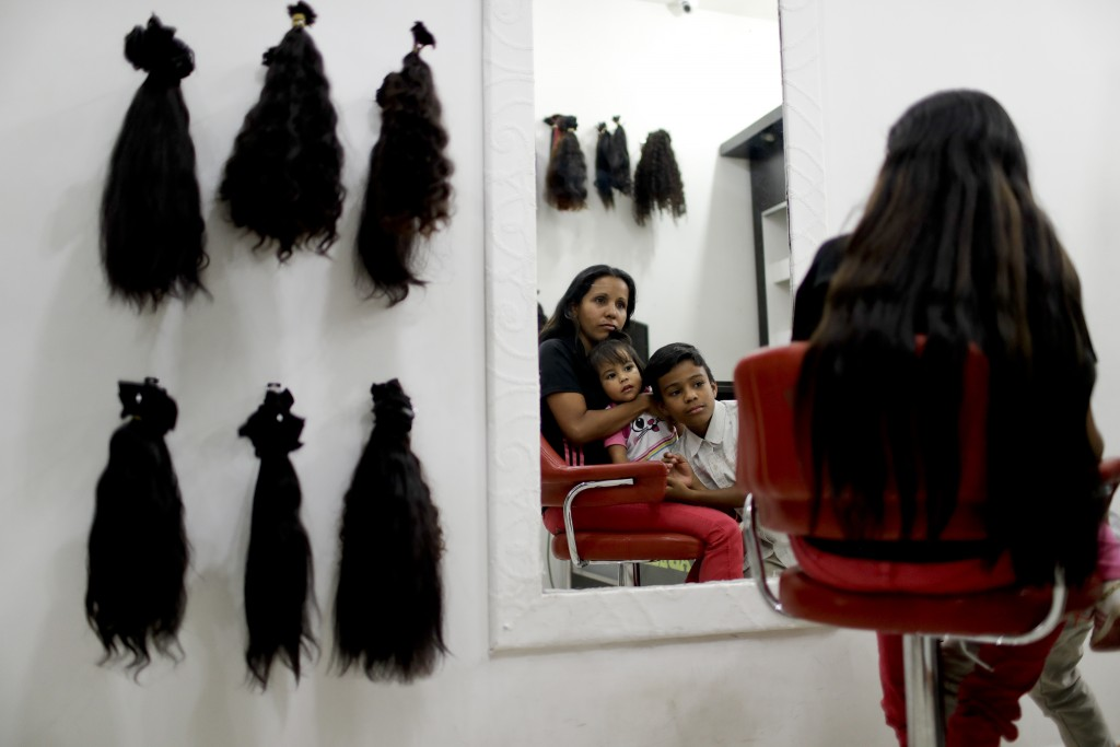 Nelly Navarro sits with her kids Nerianny and Luis in a beauty salon where she came to consult how much money she could get for her hair, in Caracas,