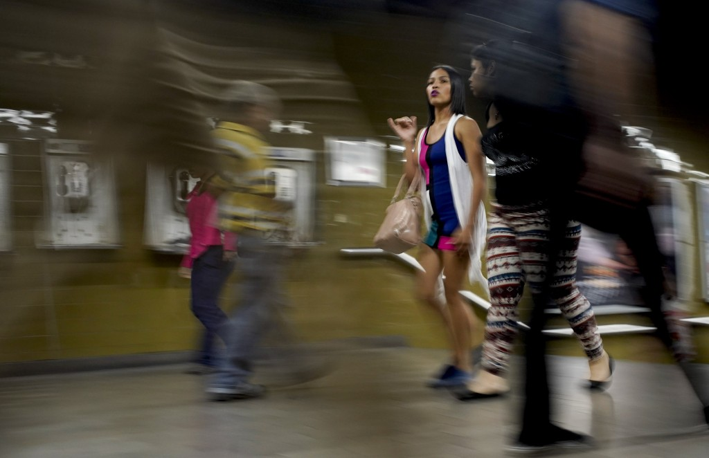 A woman wearing makeup and with her hair straightened walks through the subway in Caracas, Venezuela, Friday, March 22, 2019. While the beauty industr
