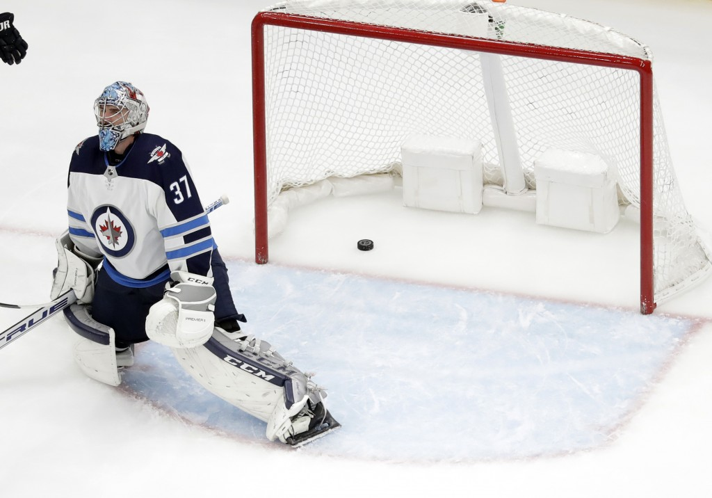Winnipeg Jets goaltender Connor Hellebuyck pauses after giving up a goal to St. Louis Blues' Jaden Schwartz during the third period in Game 6 of an NH