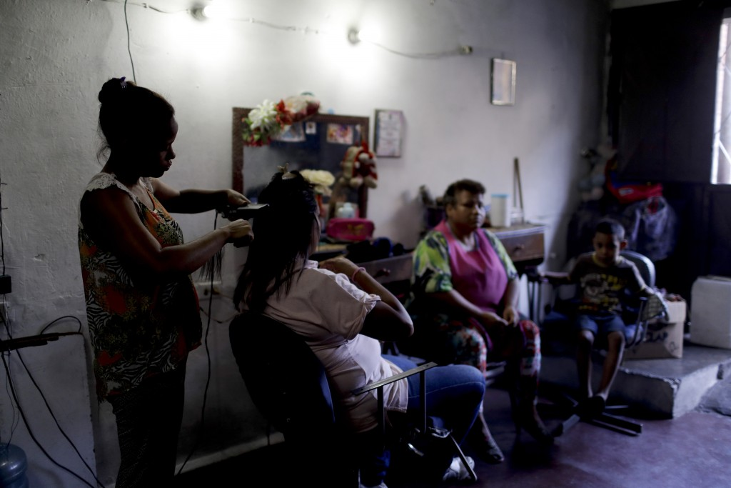Hair dresser Rosevel Velazquez attends a customer at her beauty salon, which she runs out of her home in Caracas, Venezuela, Wednesday, March 20, 2019...
