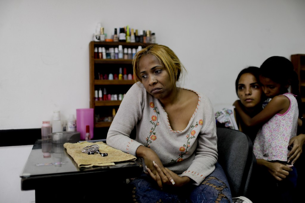 Manicurist Maria Trinidad Tobar waits for customers at a beauty salon in Caracas, Venezuela, Tuesday, March 19, 2019. Tobar said Venezuelan women no l...