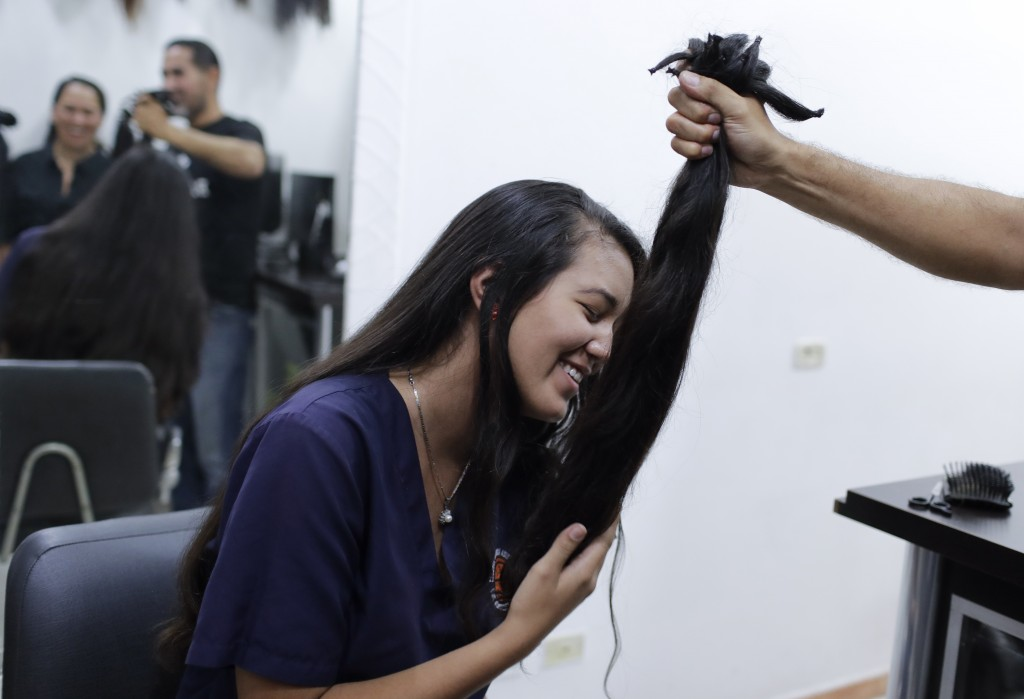 Valery Díaz holds the hair she had cut off to earn $100 in Caracas, Venezuela, Friday, April 5, 2019. After a drastic cut of 60 centimeters that was r...