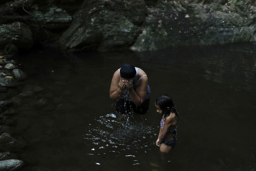 Liz Vargas and her niece Camila Vargas bathe on the skirt of a mountain in Avila National Park in Caracas, Venezuela, Thursday, April 4, 2019. Vargas ...