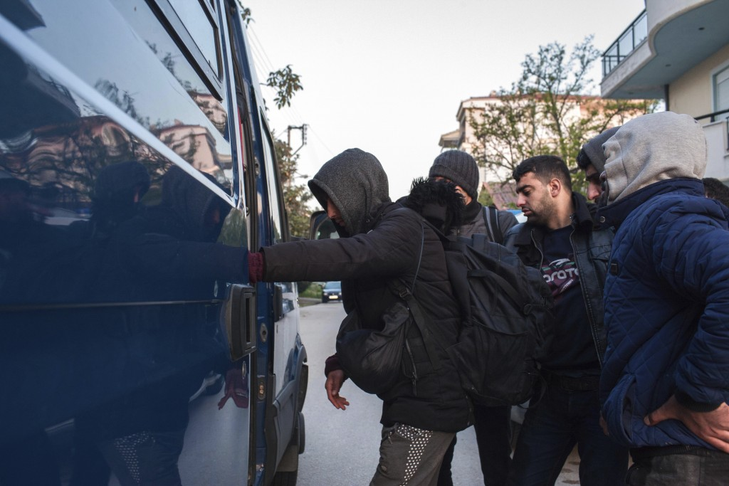 Migrants from Syria and Iraq wanting to register for asylum, embark a police bus in Orestiada town, northeastern Greece, Monday, April 22, 2019. Greek...