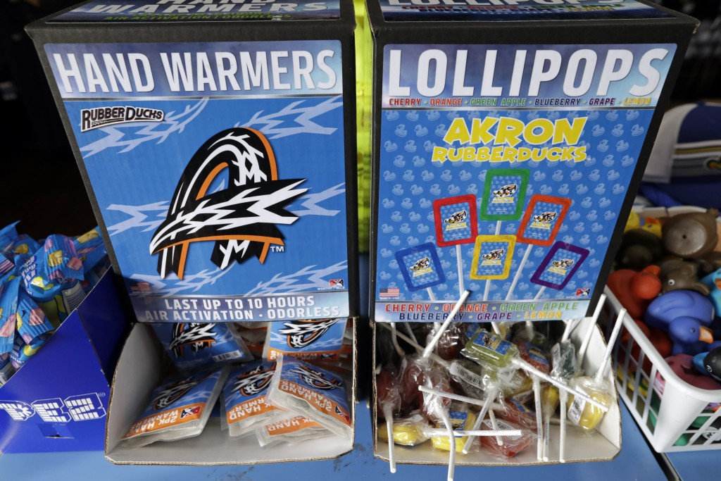 Branded hand warmers and lollipops are displayed for sale in the Akron RubberDucks team shop before a minor league baseball game between Akron and Bow...