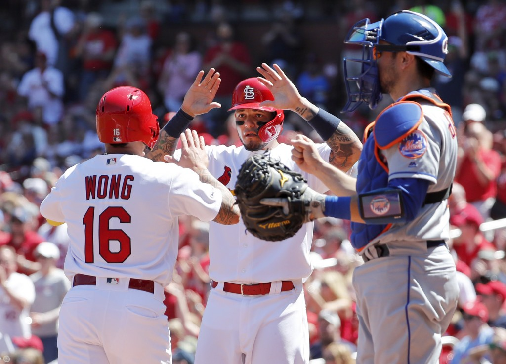 St. Louis Cardinals' Kolten Wong, left, and teammate Yadier Molina celebrate after scoring past New York Mets catcher Travis d'Arnaud, right, during t