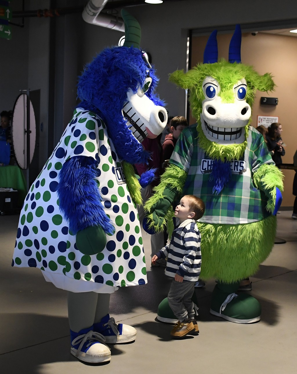 Hartford Yard Goats mascots Chew Chew, left, and Chompers greet a small fan during a game between the Yard Goats and Richmond Flying Squirrels at Dunk...