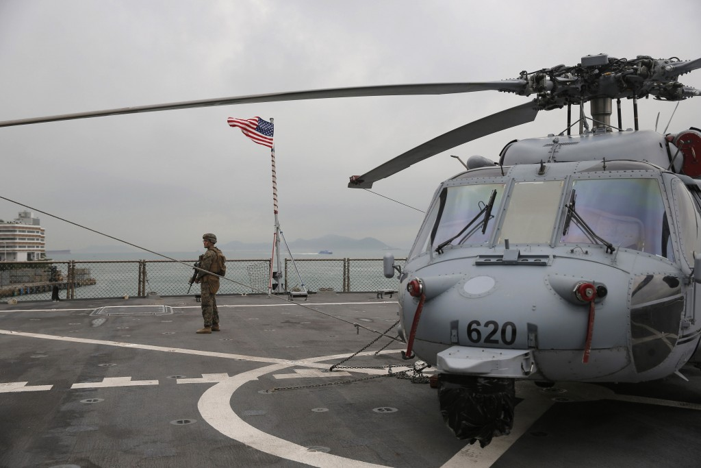 In this April 20, 2019, file photo, a U.S. marine patrols on the deck of the USS Blue Ridge, flagship of the U.S. Seventh Fleet, during a port call in
