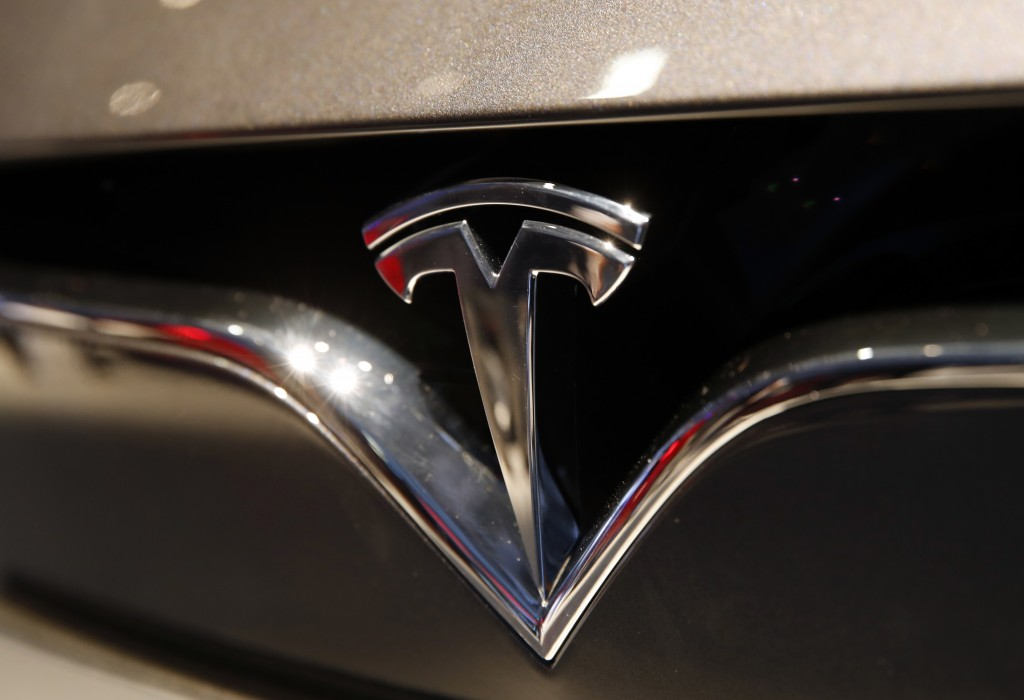 FILE- This Oct. 3, 2018, file photo shows a Tesla emblem at the Auto show in Paris. Tesla CEO Elon Musk appears poised to transform the company's elec