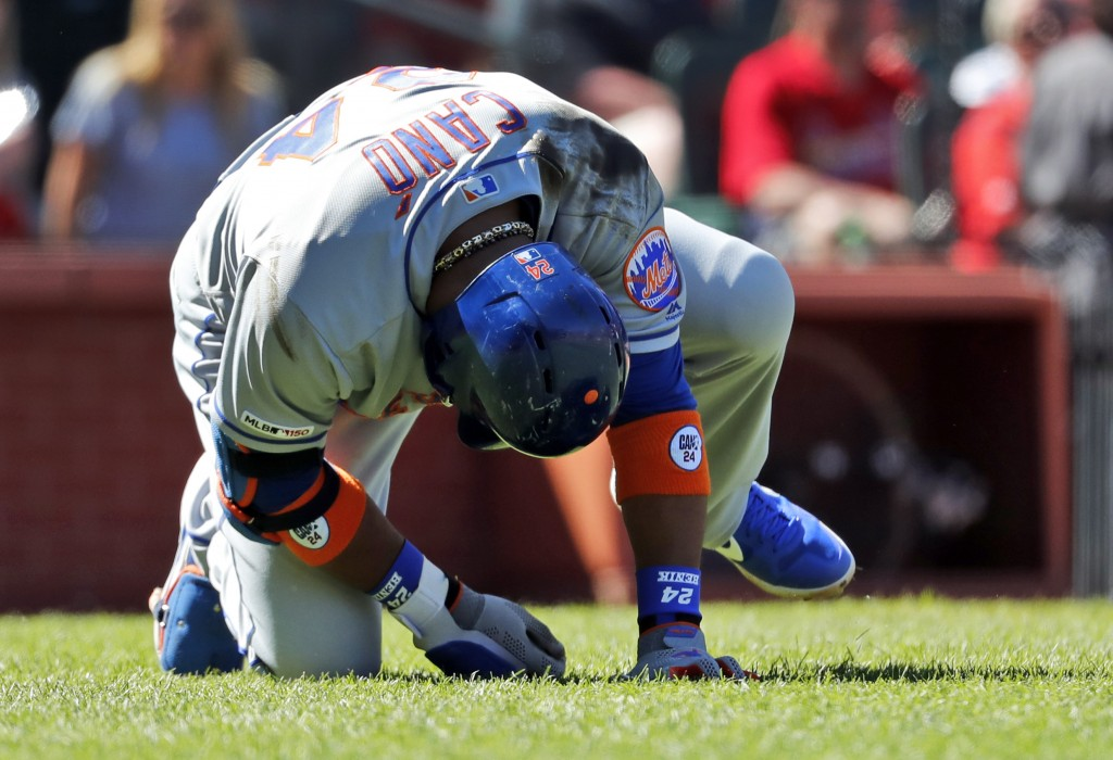 New York Mets' Robinson Cano doubles over after being injured while batting during the seventh inning of a baseball game against the St. Louis Cardina