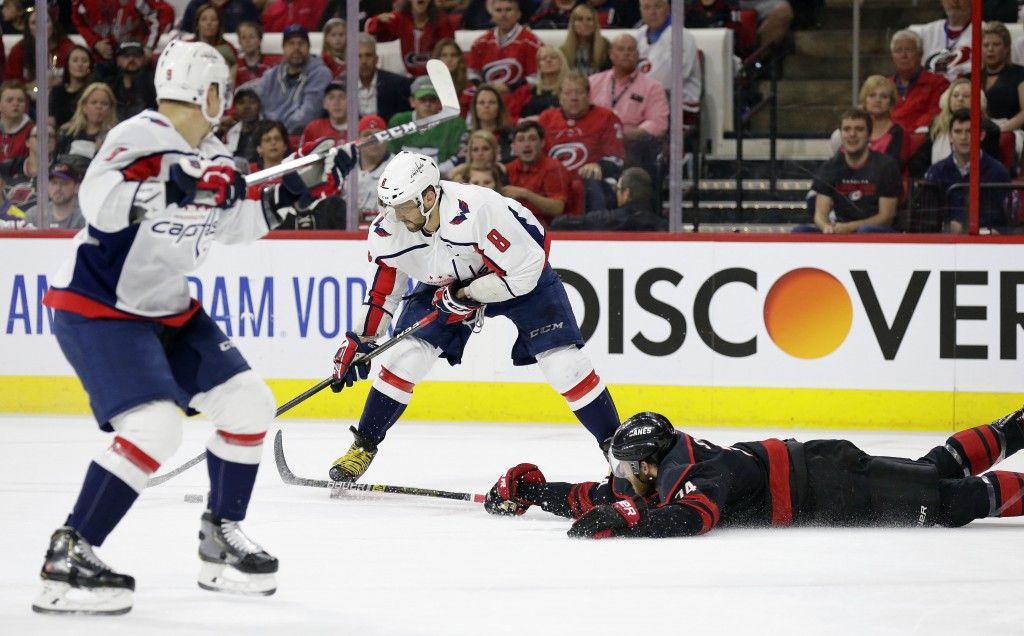 Carolina Hurricanes' Jaccob Slavin (74) falls to the ice while defending against Washington Capitals' Alex Ovechkin (8), of Russia, during the first p