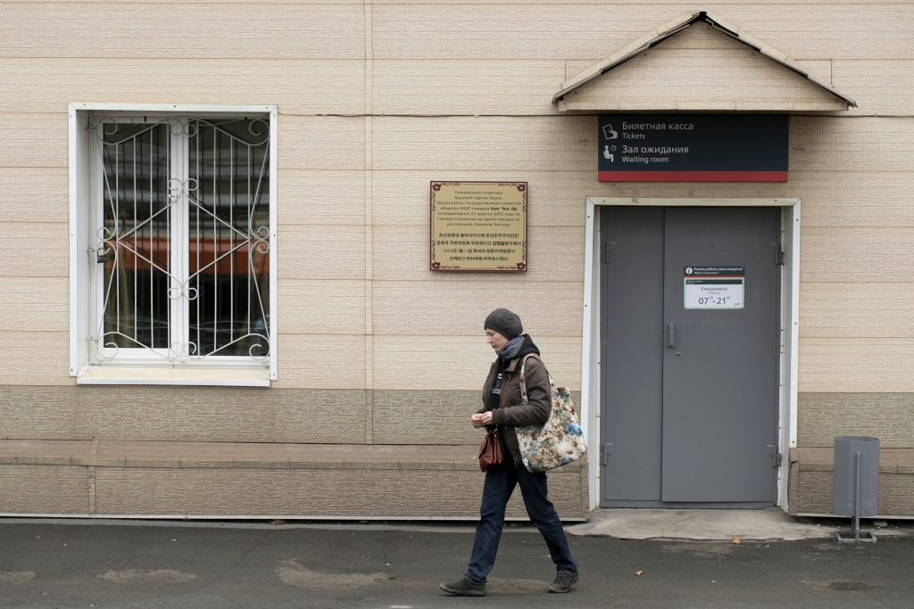A woman walks past the Memorial plaque in memory of North Korean leader Kim Jong Il's visit to Russia in 2002, at the Okeanskaya railway station where...