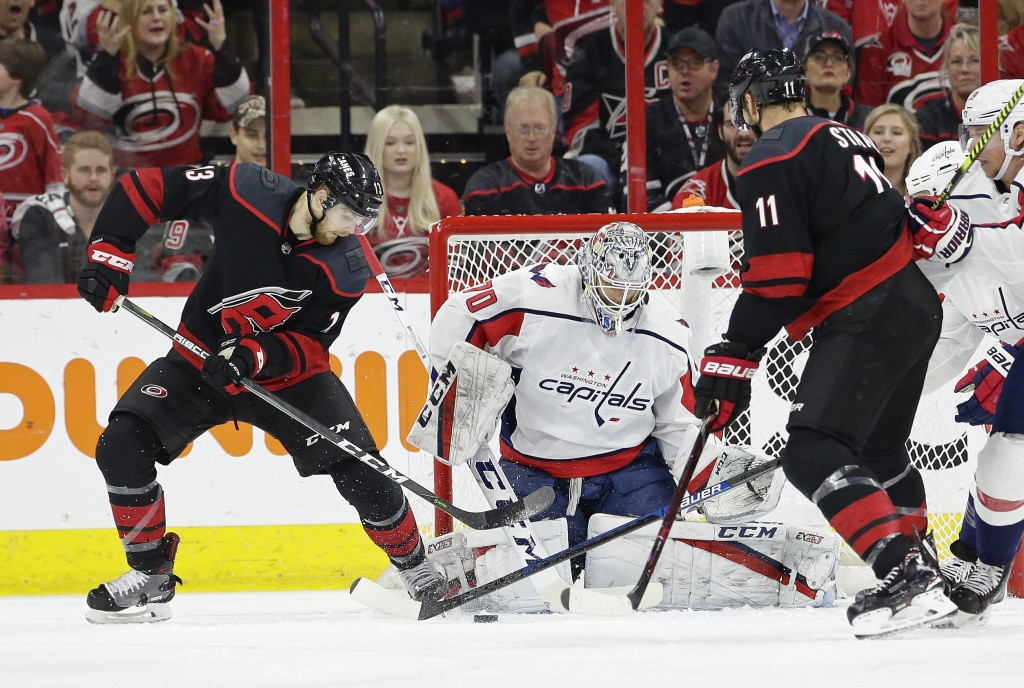 Carolina Hurricanes' Warren Foegele (13) tries to score against Washington Capitals goalie Braden Holtby (70) while Hurricanes' Jordan Staal (11) assi