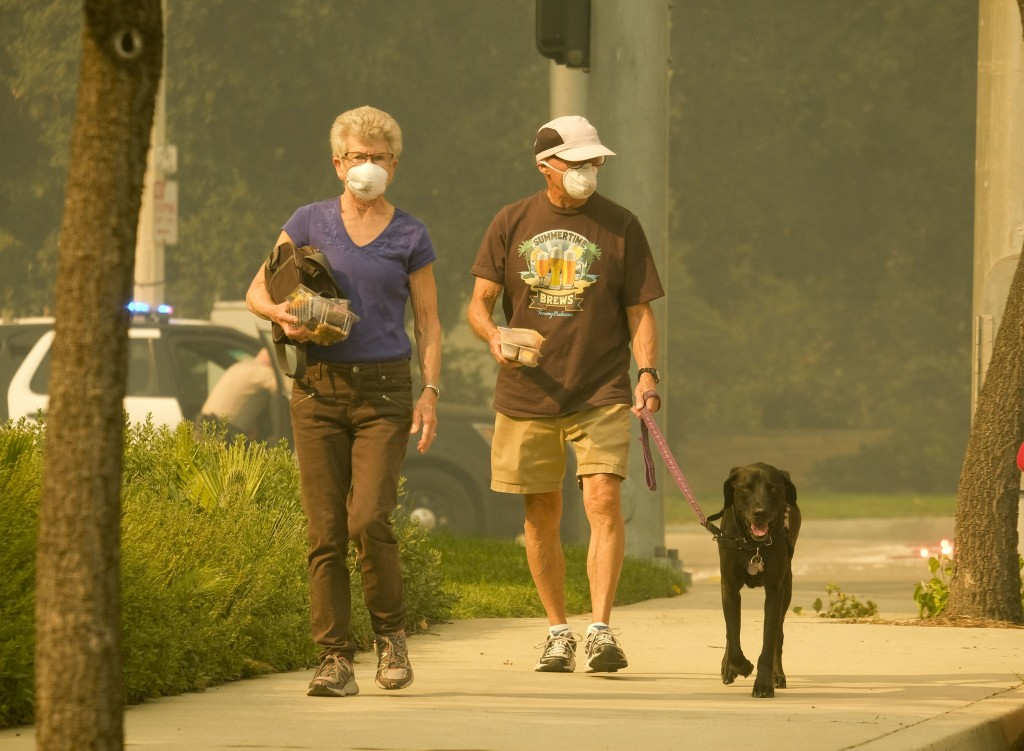 FILE - This Nov. 9, 2018, file photo people cover their faces walk their dog as smoke from a wildfire fills the air during the Woolsey Fire in Malibu,...