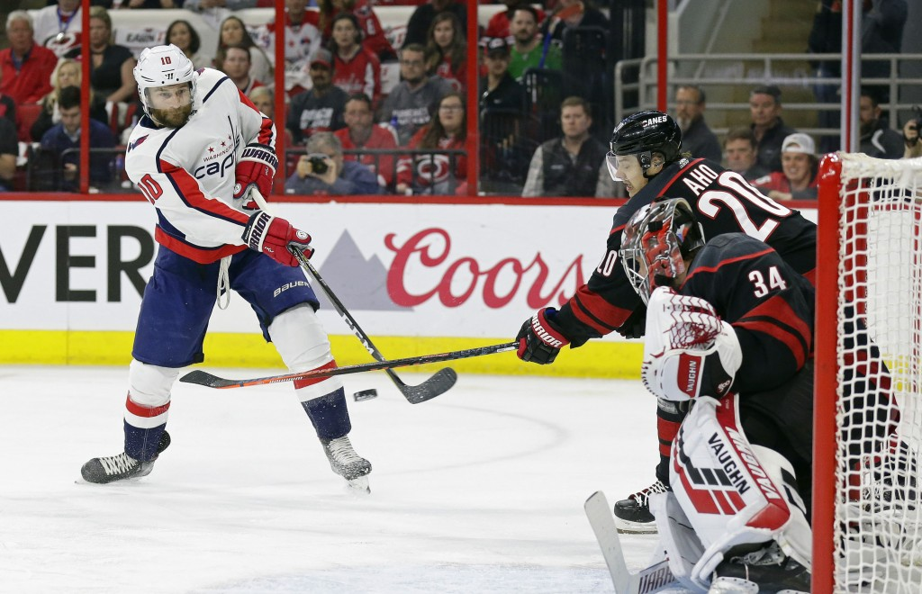 Washington Capitals' Brett Connolly (10) shoots and scores against Carolina Hurricanes goalie Petr Mrazek (34), of the Czech Republic, while Hurricane