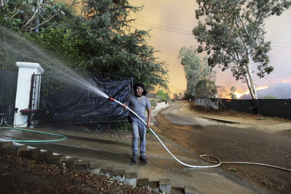 FILE - In this Nov. 9, 2018, file photo, Orlando Verganza wets down a property as flames from a wildfire, known as the Woolsey Fire, approach in Malib...