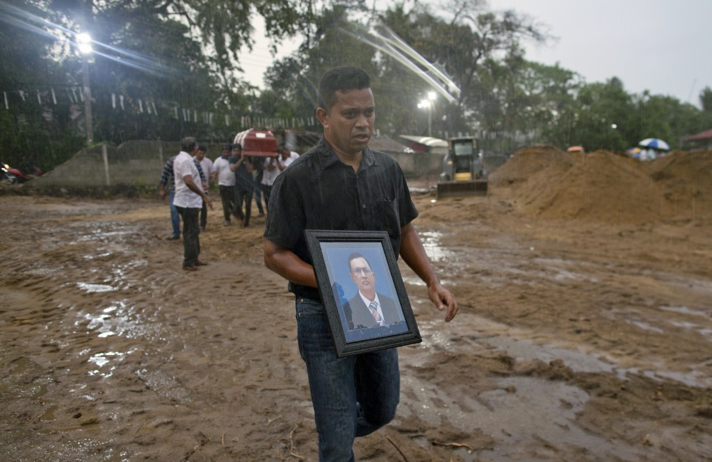 A relative carries a portrait of Calistas Fernando ahead his coffin for burial during the funerals of three people of the same family, all died at Eas...
