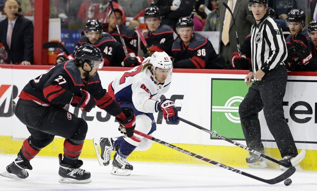 Carolina Hurricanes' Justin Faulk (27) and Washington Capitals' Carl Hagelin (62), of Sweden, chase the puck during the first period of Game 6 of an N...