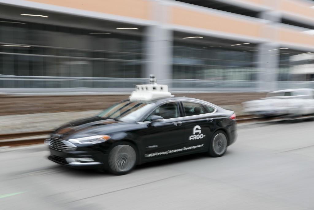 In this Jan. 4, 2019, photo made with a slow shutter speed, one of the test vehicles from Argo AI, Ford's autonomous vehicle unit, navigates through t...