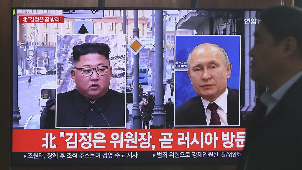 A man passes by a TV screen showing images of North Korean leader Kim Jong Un, left, and Russian President Vladimir Putin, right, during a news progra...