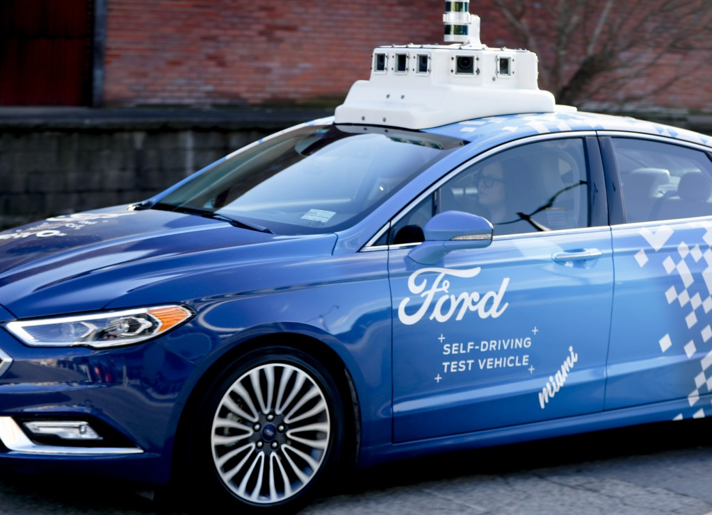 In this Dec. 18, 2018, photo, one of the test vehicles from Argo AI, Ford's autonomous vehicle unit, navigates through the strip district near the com...