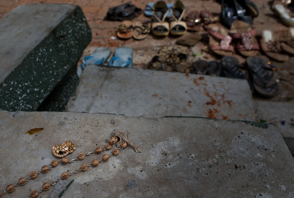 In this April 22, 2019, file photo, a set of rosary beads, footwear and personal belongings of victims are scattered at the scene of a suicide bombing