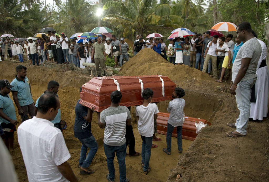 Relatives carry a coffin for burial during the funerals of three members of the same family, all died at Easter Sunday bomb blast at St. Sebastian Chu...