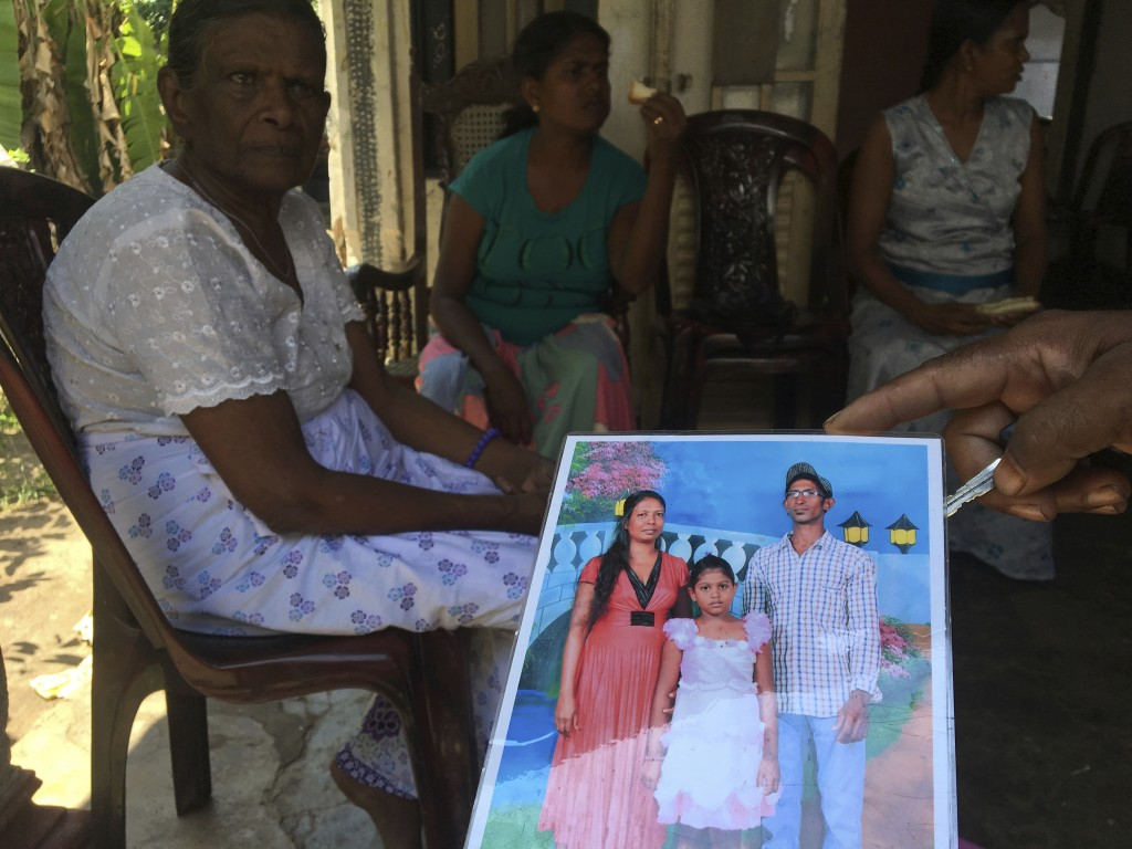 A family friend shows an image of Easter Sunday bomb blast victim Dileep Roshan, right in photo, who left behind a wife and daughter, in Negombo, Sri ...
