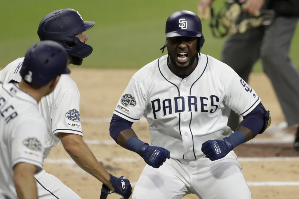 CORRECTS INNING TO SECOND INNING INSTEAD OF 22ND INNING - San Diego Padres' Franmil Reyes, right, reacts with teammates after hitting a two-run home r...